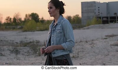 Brunette girl in the denim jacket is on wasteland