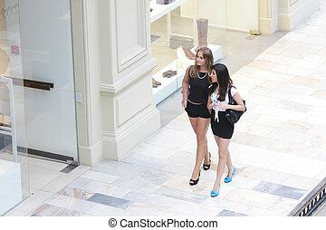 Walking along shoe shops - Two young pretty walking along...