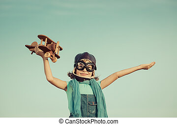 Happy child playing with wooden toy airplane