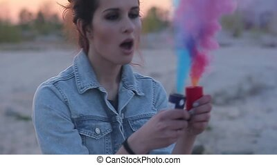 Girl inflates colored smoke bombs.
