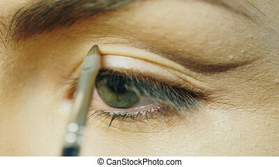 Impose makeup on the eyes of a young girl