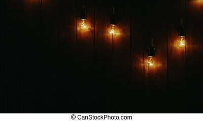 Garland of light bulbs on a wooden background - On a dark...
