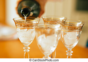 Pouring champagne into a glasses standing on table with...