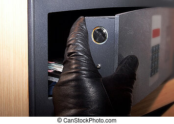 Theft - Thiefs hand reaching out for money in a safe