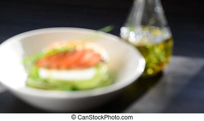 salad with tomatoes cheese and herb - olive oil pouring over...