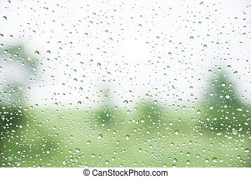 natural water drops on window glass with green