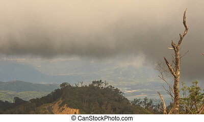 Thick Black Rainy Clouds above Woody Hills in Tropics -...