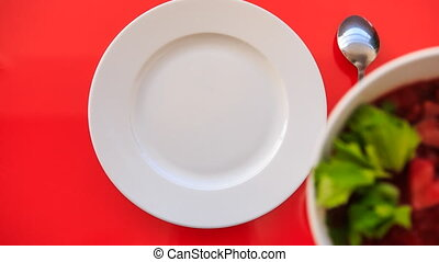 Hands Put Bowl of Ukrainian Soup Borsch to Plate on Red...