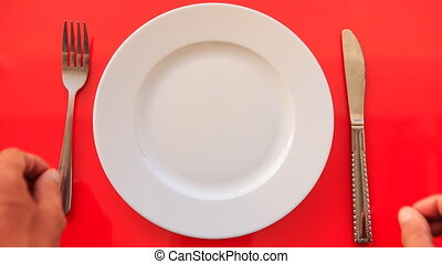 Hands Put Fork Knife Horizontally on Plate on Red Table -...