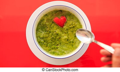 Hand Takes Red Heart away of Green Soup on Red Table -...