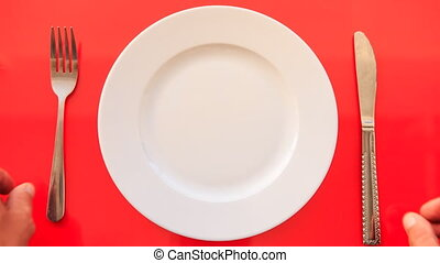 Hands Put Fork Knife Crosswise on Plate on Red Table -...