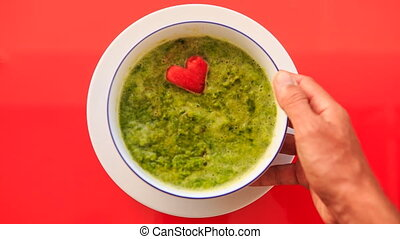 Hand Sets Bowl of Green Soup Straight on Red Table - closeup...