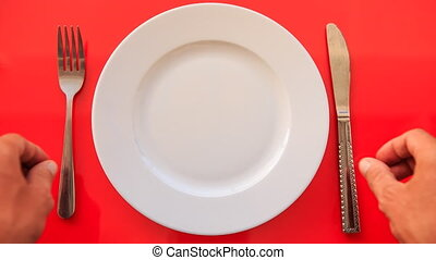 Hands Put Fork Knife Vertically on Plate on Red Table -...