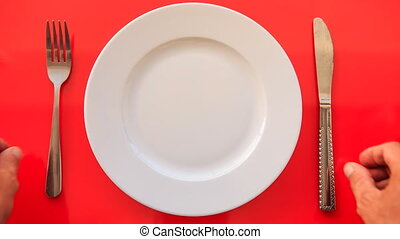 Hands Put Fork Knife at Acute Angle on Plate on Red Table -...