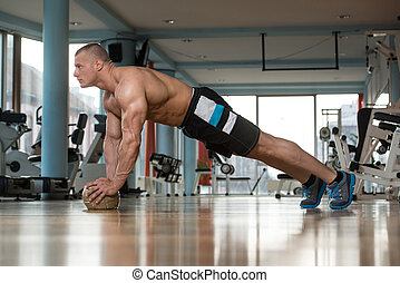 Young Man Doing Press Ups On Fitness Ball - Young Adult...