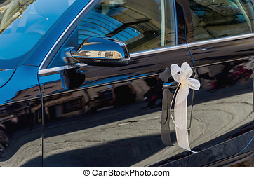 Car door decorated with ribbon bow for a marriage