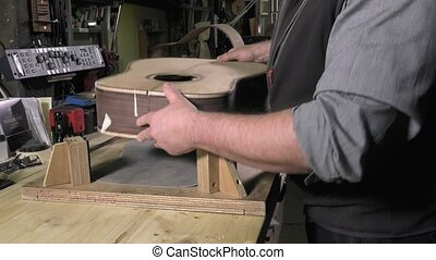 Master luthier guitars at work - positioning the body of the...