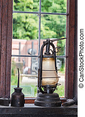 Old kerosene lamp on a window sill in the background a...