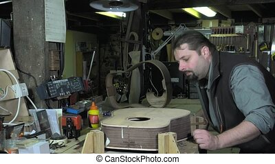 Master luthier guitars at work - sanding increasingly end of...