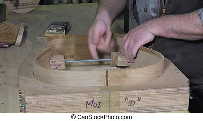 Master luthier guitars at work - positioning splint guitar...