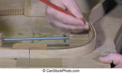 Master luthier guitars at work - leveling the edges of the...
