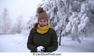 Woman throwing a snowball into the camera in slow motion -...