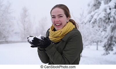 Woman blows off snow from hands