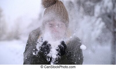 Woman blows off snow into the camera