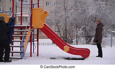 Parents play with their child on a roller coaster in winter,...