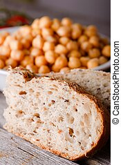 Detail of wholewheat bread in front of bowl with chickpeas -...