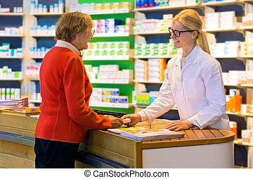 Customer receiving medication from pharmacist - Happy senior...