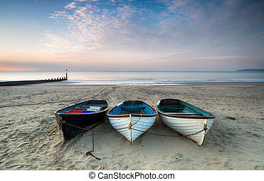 Boats on Bournemouth Beach - Three wooden fishing boats on...