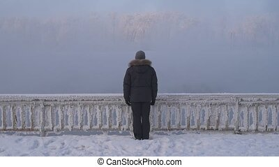 Man standing on the misty river bank