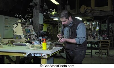 Master luthier guitars at work - Repair key pad of an old...