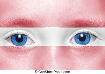 human's face with latvian flag