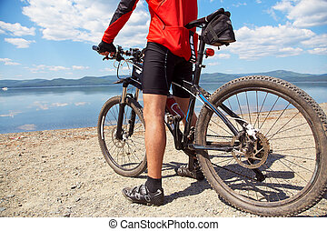 man with bike on a mountain lake