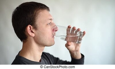 Man drinking water - Young man is drinking a glass of water....