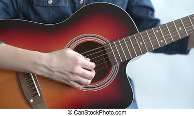 Close up of a guitar player - Young woman in a denim dress...