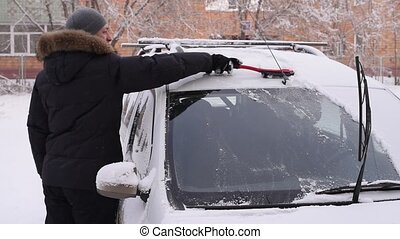 Man cleaning the car from the snow - Man is cleaning the car...
