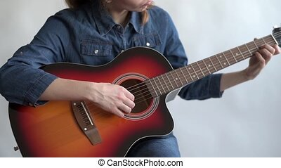 Woman learning to play the guitar - Young woman in a denim...