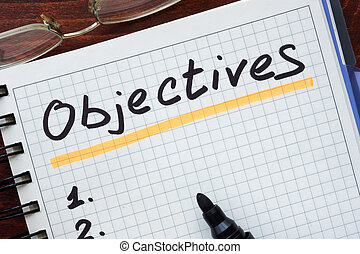 Objectives concept written in a notebook on a wooden table
