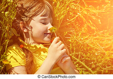 girl lying in the grass with dandelion