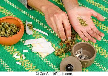 Rolling a joint - Female hands rolling a joint surrounded by...