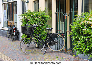 Parked bicycles near the old houses on the narrow street