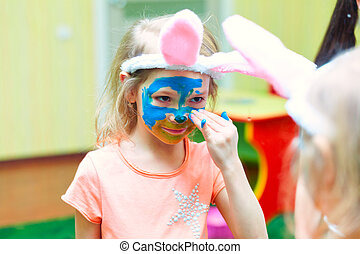Happy cute toddler painting her face with gouache paints
