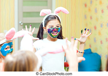 Happy cute toddler painting her face with gouache paints -...