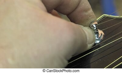 Master luthier guitars at work - replacement strings on an...