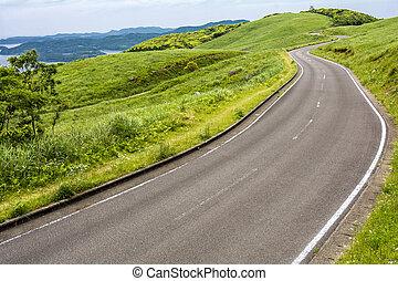 Roadway on hillside - Roadway on seashore green hillside in...