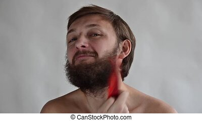 Handsome man brushing his beard