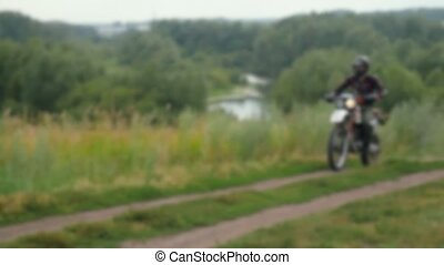 Brutal young man drive the motorcycle on the field with a helmet in slowmotion. Blurred background